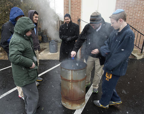 "As son Asher, 13, watches (far right) Rabbi Noam Stein of Memphis, Tennessee (second from left) drops his bag of ""chametz - or leavened food products into a fire, during an annual burning in the rear of Congregation Sons of Israel on Monday's snowy morning. The ritual, which dates to biblical times, is based on the obligation that all Jews have to rid themselves of chametz by the morning before Passover each year."