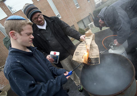"As son Asher, 13, (left) helps his father, Rabbi Noam Stein of Memphis, Tennessee, to ignite a fire to burn his bag of ""chametz - or leavened food products, during an annual burning in the rear of Congregation Sons of Israel on Monday's snowy morning. The ritual, which dates to biblical times, is based on the obligation that all Jews have to rid themselves of chametz by the morning before Passover each year."