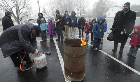 "Jonathan Powers of Allentown (far left) prepares to use a torch to burn ""chametz - or leavened food products in the rear of Congregation Sons of Israel on Monday's snowy morning."