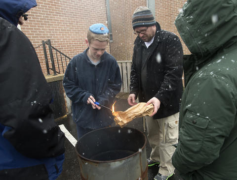 "As son Asher, 13, (left) helps his father, Rabbi Noam Stein of Memphis, Tennessee, to ignite a fire to burn his bag of ""chametz - or leavened food products, during an annual burning in the rear of Congregation Sons of Israel on Monday's snowy morning."