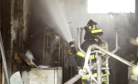 Hampton fire personnel work on knocking down a fire on Smith St. Tuesday afternoon.