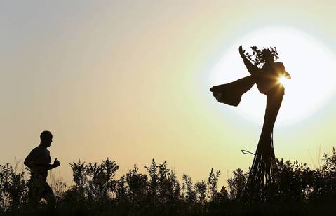 The sunrises over a runner, and a Daphne Garden sculpture by artist Dessa Kirk, at Northerly Island in Chicago on a warm September morning.
