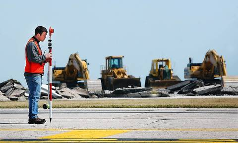 A surveyor measures the remaining area of Meigs Field to ensure that it is safe for the 16 stranded air planes to takeoff. The runway at the airport was dug up by the city to effectively end flights at Meigs Field.
