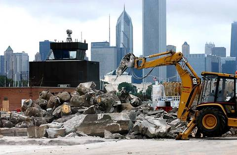 Demolition crews use heavy equipment to tear up pieces of concrete at Meigs Field