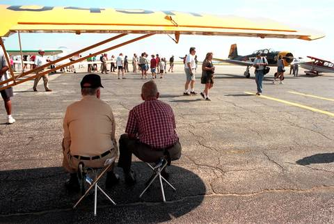 Eugene Wisniewski, left, of Indian Head Park, Ill., sits under the wing of his cousin's Piper J3 with friend Mike Bogal, of Chicago, during the 4th Annual Friends of Meigs Field Open House. Sunday has been declared, ironically, ``Meigs Field Day'' in the City of Chicago in which the lakefront airport celebrated its 50th birthday.