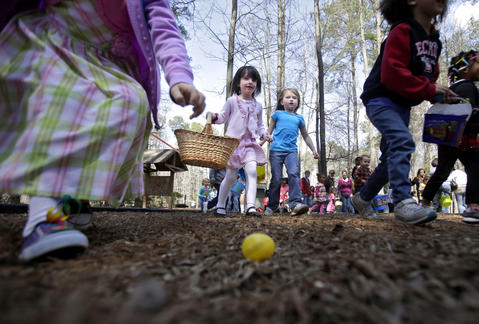 Eleanor Armstrong, 6, left of Newport News reaches down to pick up a plastic egg as Chloe Finamore, 4, center left, and Chloe Phelps, 6, center right, search Sandy Bottom Nature Park for eggs during Saturday's Easter egg hunt.