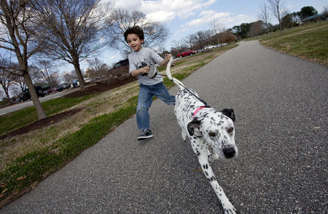 Six-year-old Gavin Garcia runs with Eevee, a Dalmation-Lab mix, at Riverview Farm Park on Monday afternoon.