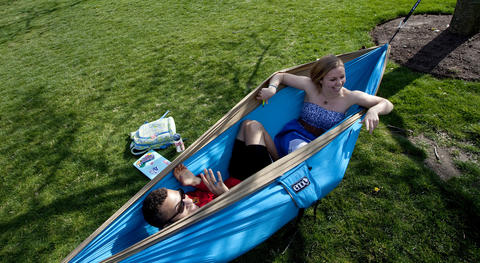 Davant Marshall and Kayla Vande Vrede soak up the mid-afternoon sun in a friend's hammock on the campus of Christopher Newport University on Monday.