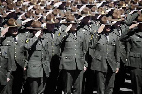 Illinois State Police Troopers salute 28-year-old Trooper James Sauter at his funeral ceremony at Moraine Valley Church in Palos Heights, Ill. Sauter was killed Thursday when a semitrailer hit his squad car on I-294 in Glenview.