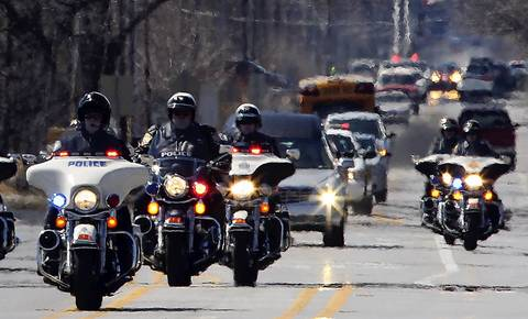 A police motorcade leads the way for the hearse containing the casket of Illinois State Police Trooper James Sauter, 28, as hundreds of local and state police cars pass in procession along 127th St. near route 83 in Crestwood, Ill.
