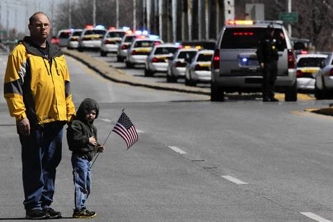 Tom Novak and his son Kyle, 4, pay their respects to Illinois State Police Trooper James Sauter, 28, as hundreds of local and state police cars pass in procession along 127th St. near route 83 in Crestwood, Ill. Sauter was killed when a semitrailer hit his squad car on I-294 in Glenview.