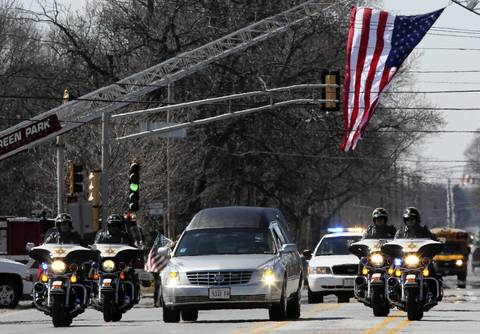 A police motorcade leads the way for the hearse containing the casket of Illinois State Police Trooper James Sauter, 28, as hundreds of state and local police cars pass in procession along 127th St. near route 83 in Crestwood, Ill. Sauter was killed Thursday when a semitrailer hit his squad car on I-294 in Glenview.