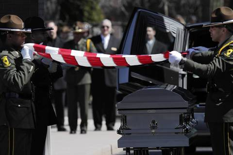 The Illinois State Police honor guard folds a flag over 28-year-old Trooper James Sauter's casket after his funeral ceremony at Moraine Valley Church in Palos Heights, Ill. Sauter was killed Thursday when a semitrailer hit his squad car on I-294 in Glenview.