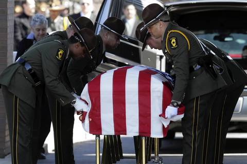 The Illinois State Police honor guard folds the flag over 28-year-old Trooper James Sauter's casket after his funeral ceremony at Moraine Valley Church in Palos Heights, Ill. Sauter was killed March 28, 2013, when a semitrailer hit his squad car on I-294 in Glenview.