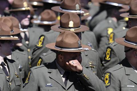 Illinois State Police Troopers honor 28-year-old Trooper James Sauter at his funeral ceremony at Moraine Valley Church in Palos Heights, Ill.