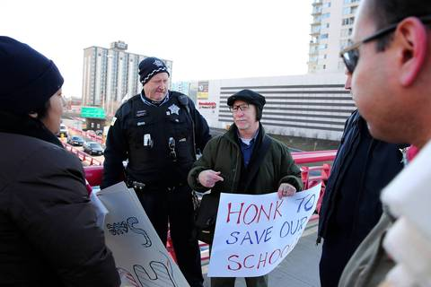 Protesters, including Howard Emmer, center, are escorted by police from the Washington Street overpass on the Kennedy Expressway after being asked to leave. About 10 protesters held signs in support of the 61 school buildings that Chicago school officials plan to close.