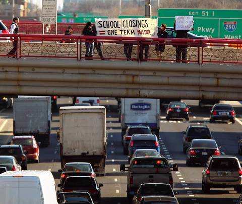 Protesters hold a sign in support of the 61 school buildings that Chicago school officials plan to close on the West Madison Street overpass above the Kennedy Expressway.