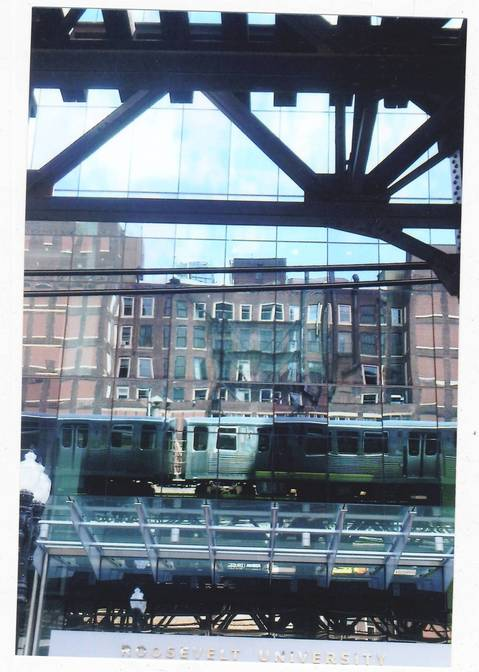 Reflections of a CTA train on the facade of a Roosevelt University building.