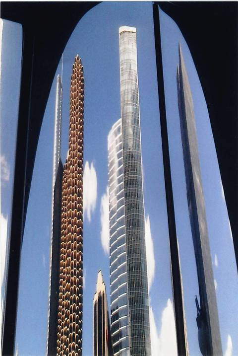 Marina City, Trump Tower and other buildings are reflected off a building's exterior across the street.
