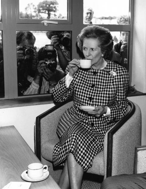 British Conservative Prime Minister Margaret Thatcher, watched by the press, enjoys a cup of tea at the opening of the South Mimms Motorway service area in 1987.