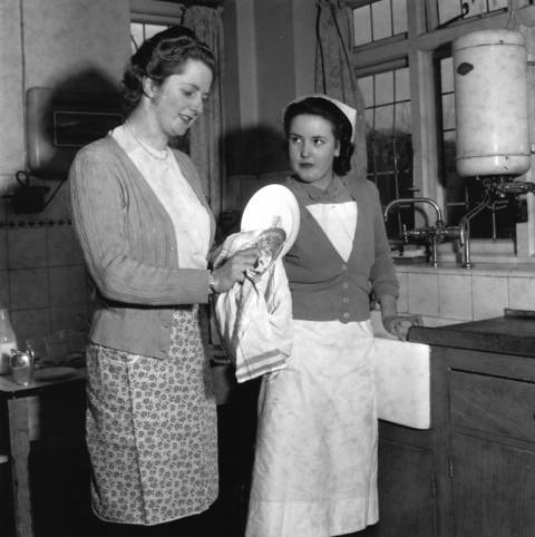 Conservative politician and future prime minister Margaret Hilda Thatcher, dries dishes with a nurse.