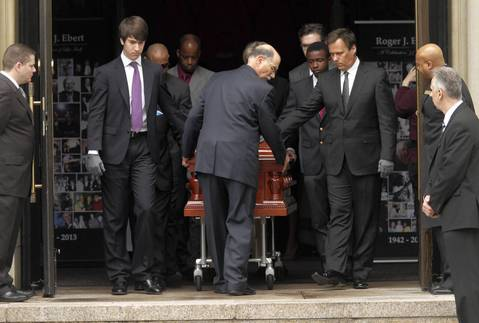 Pallbearers, including Richard Roeper, right, guide Roger Ebert's casket outside Holy Name Cathedral in Chicago after Ebert's funeral.