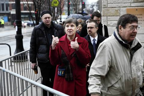 Peggy Callahan, of Chicago, joins about 100 people waiting in line outside Holy Name Cathedral in Chicago for Roger Ebert's funeral.