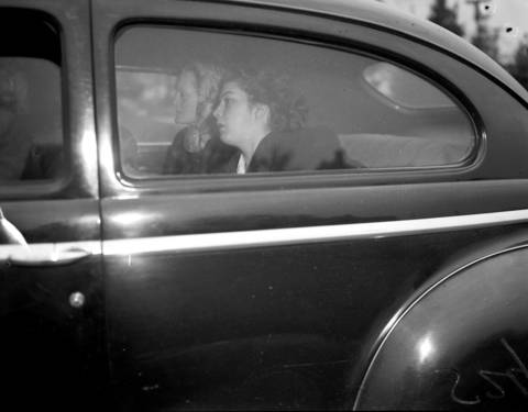 Grace Rinearson, 19, rides away in a car after identifying the body of her sister Roberta Rinearson, 10, who was murdered on Dec. 17, 1948.