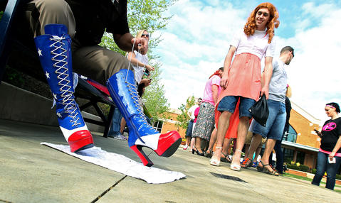 Jason Wells watches as Newport News sheriff deputy Cpl. William Churchill gets his boots on for the Walk a Mile in Her Shoes event Saturday at Peninsula Town Center. The walk gets men involved in preventing violence against women and raises money for the Center for Sexual Assault Survivors.
