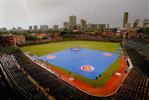 Lightning strikes kiss the Lakeview skyline as the Wrigley Field infield is covered in tarp during a rain delay in 1999 game against the White Sox.