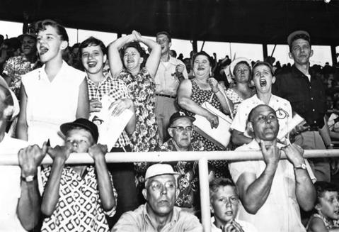 A lone Milwaukee Braves fan, center, sits amid cheering Cubs fans in 1955.