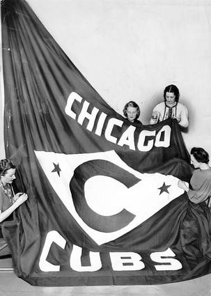 """Jean Brooks, Mildred Olson, Dorothy Short and Elise Allen of the Wrigley Company sew """"pennant stars"""" onto a new Cub flag in February 1938."""