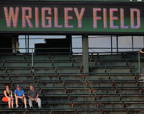 A few Cubs fans sit in the bleachers.