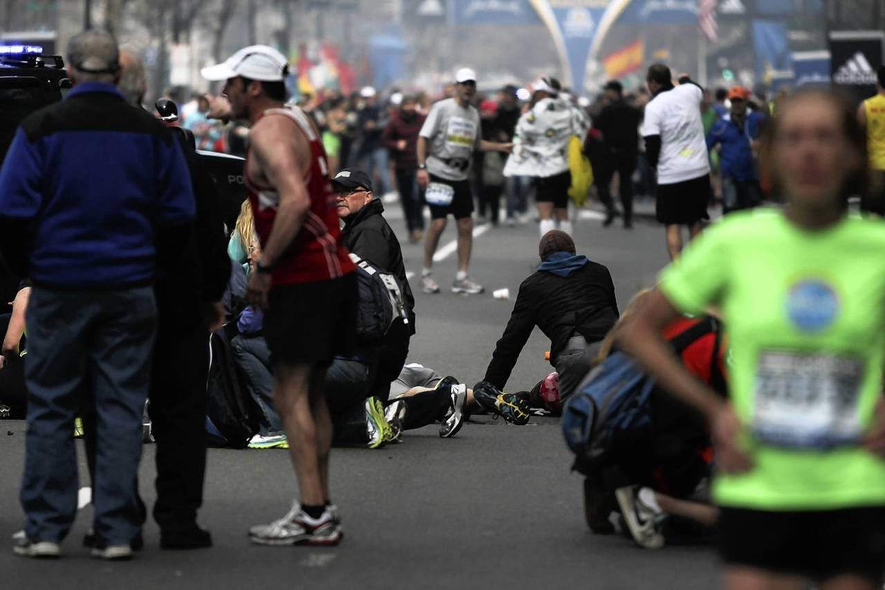Injured people are attended to at the scene of an explosion at the Boston Marathon.