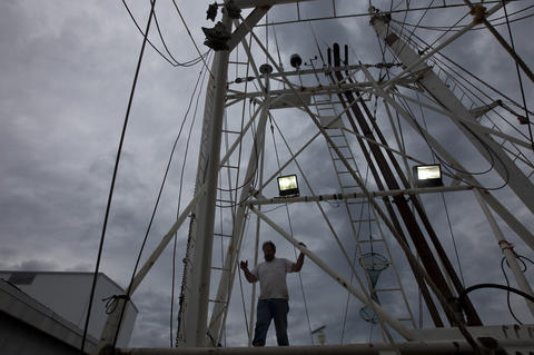 Ivan Gillikan prepares rigging to raise a stabilizer aboard the Tamara Alane at the docks of L.D. Amory & Co. in downtown Hampton on Monday. The boat, based in Hobucken, NC, pulls in flounder, scallops and shrimp.