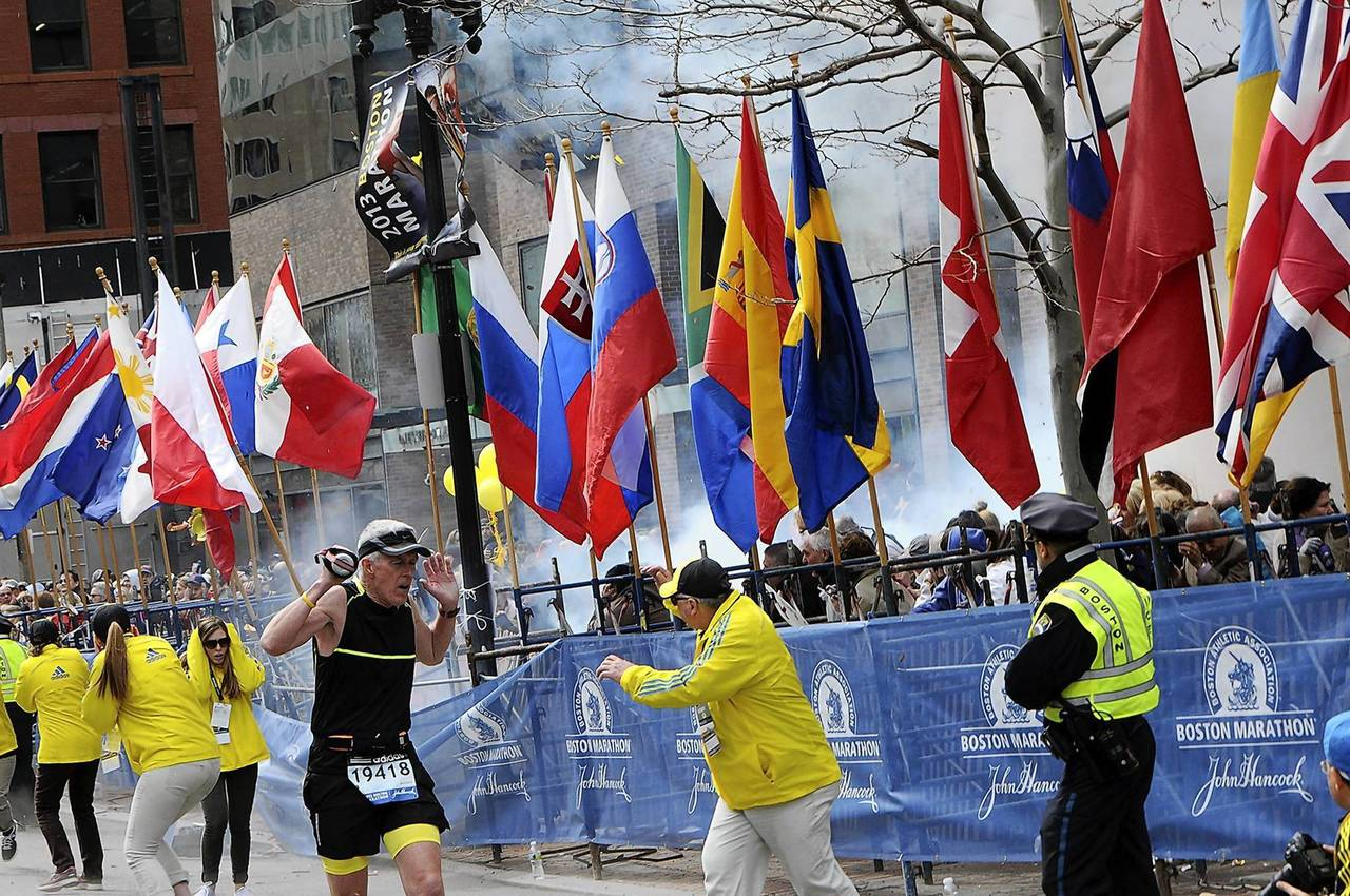 Police and runners react to an explosion during the Boston Marathon finish area.