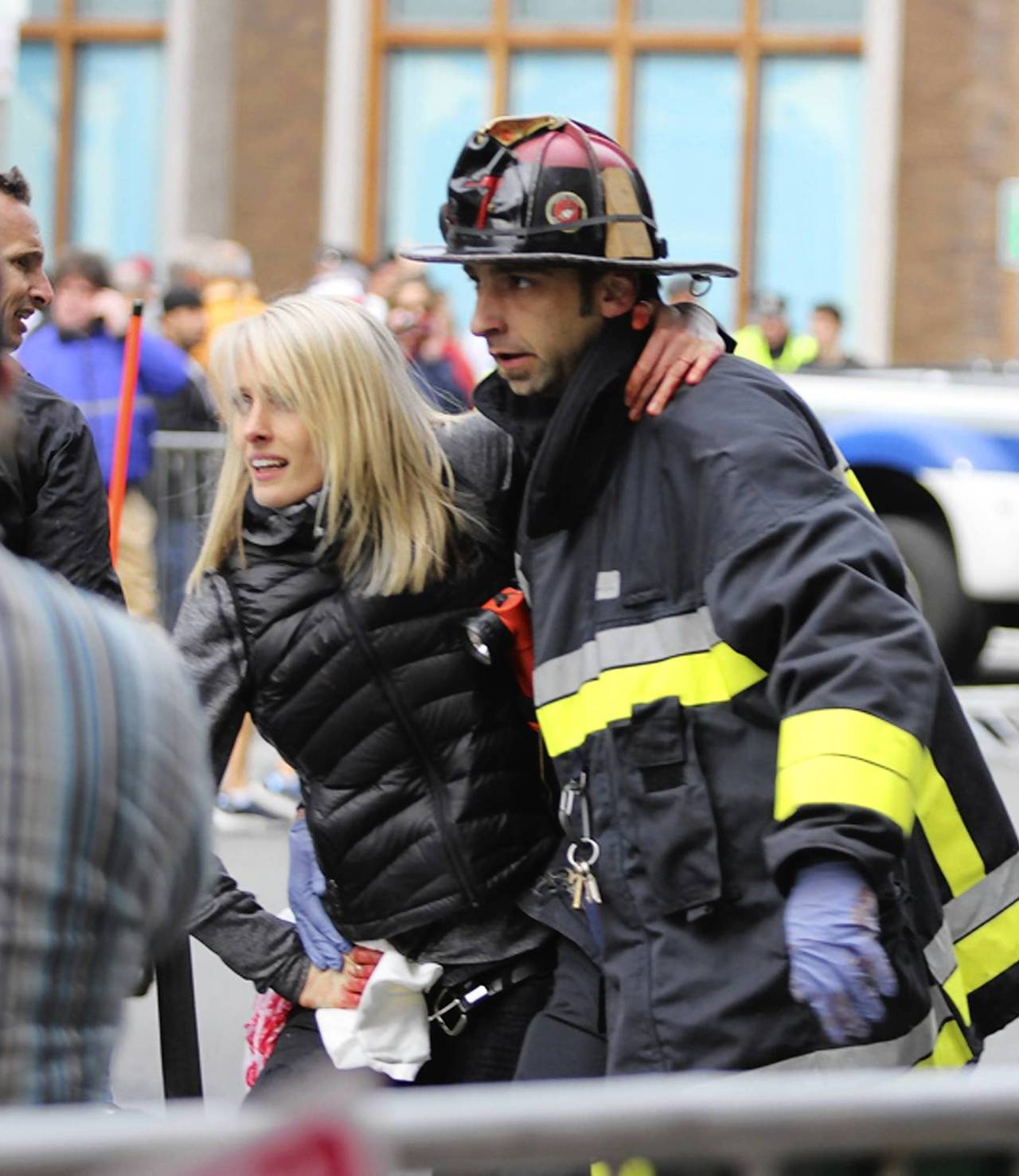 An injured woman is attended to at the scene of an explosion at the Boston Marathon.