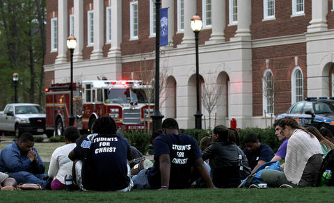 Christopher Newport University students hang out on the great lawn Tuesday as Newport News police and fire personel were called to the campus after several fires were set in restrooms at different buildings.