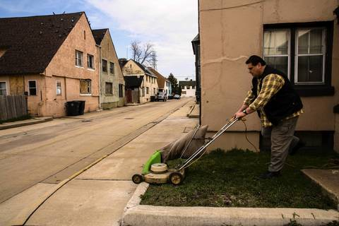 Richard Suchanuk cuts grass in front of one of his rental properties in Marktown. Many residents have deep roots in Marktown, and are trying to keep the little village alive.