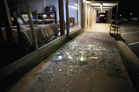 Blown out plate glass windows lay shattered on the sidewalk and street after the West Fertilizer Company exploded in West, Texas.