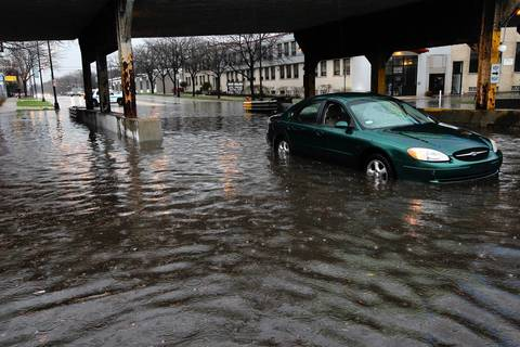 A car is stopped in high water under a viaduct on Peterson Avenue west of Pulaski Road.