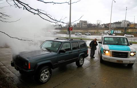"""Edward Odicho, of Skokie, hails a cab after his sport utility vehicle started smoking when he drove though a flooded off-ramp on his way to work on the Kennedy Expressway at the Addison Street accident investigation site in Chicago. """"I'm not worried about my car, I'm worried about my job,"""" said Odicho, who works in Greektown."""