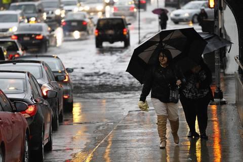 Pedestrians walk through rain-soaked sidewalks along Addison Street to the CTA Blue Line at the Kennedy Expressway.