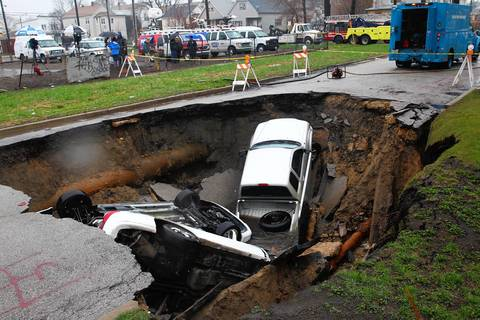 Emergency personnel stand at the site of a sinkhole at Houston Avenue and 96th Street in Chicago. Three cars were swallowed by the hole when the street caved in Wednesday afternoon. The sinkhole is the result of a water main that broke in the area and his gushing water, said Tom LaPorte, a spokesman for the Water Department. The weather and the intense rain could have aggravated a water main made from cast iron that takes back to 1915, he said. Officials aren't certain of the cause some of the factors being looked at is the age of the main and weather conditions.