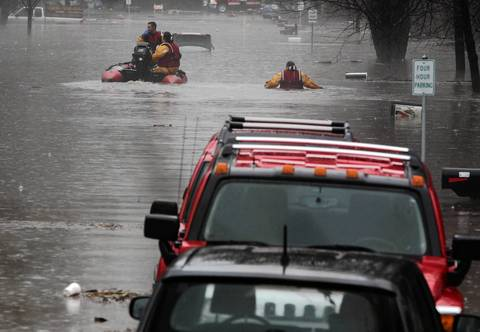 Rescue personal look for people to assist near Ogden Avenue and Route 53 in Lisle during a day of heavy flooding.