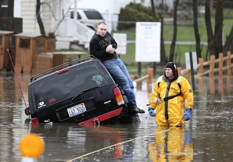 A Round Lake Area Firefighter waits with a motorist stuck in water in Round Lake Heights.