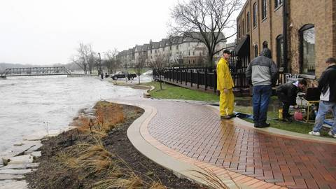 Residents and business owners pump out water next to the Fox River in St. Charles, Ill.