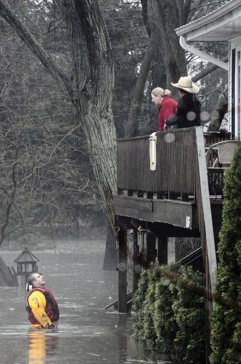 A rescuer talks to a couple at their flooded home in Lisle.