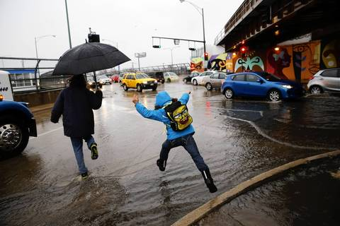 Commuters navigate a flooded intersection on Addison Street at the off ramp from the inbound Kennedy Expressway near the CTA Blue Line on Chicago's northwest side.