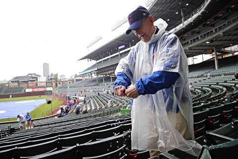 Usher Bob McCown wipes water off of seats before the Chicago Cubs face the Texas Rangers.